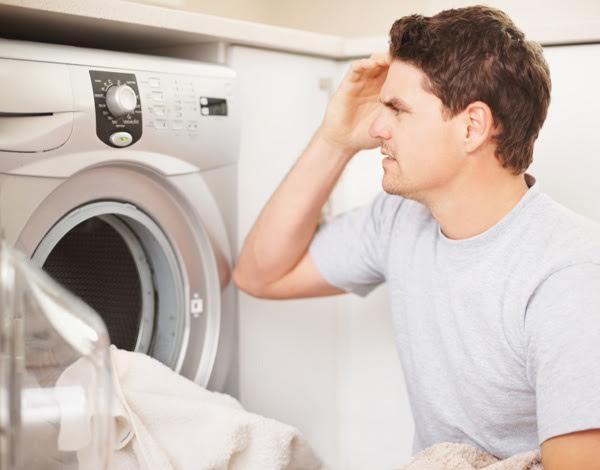 Confused handsome man adjusting the controls of the washing machine